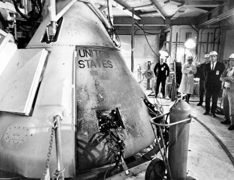 Technicians viewing the Apollo spacecraft where three flight crew members died during a launch simulation test, Cape Canaveral, Florida, 1967