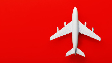 White passenger model airplane on a bright red background. Free space for text