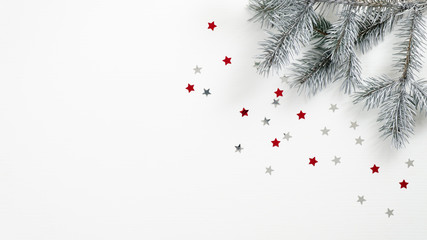 Christmas tree branch and confetti stars on white background. Flat lay, top view, copy space. Xmas banner mockup, winter holidays frame, greeting card template Wall mural