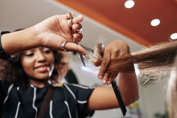 Close-up image of smiling hairdresser cutting split ends of section of hair