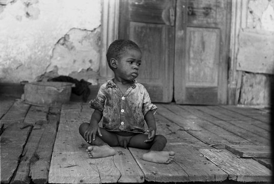 African American child on a dilapidated porch, original title: 'Negro child on porch of dilapidated Trepagnier plantation near Norco', Louisiana, photograph by Lee Russell, September, 1938