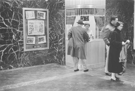 Man purchasing a movie ticket from a woman in a ticket booth as a couple stands to the side,