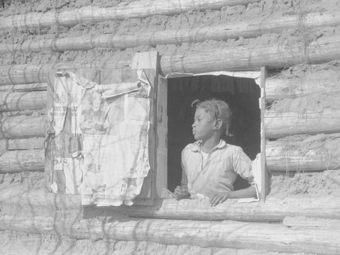 African American girl looking out the window of a plantation log cabin tenants home