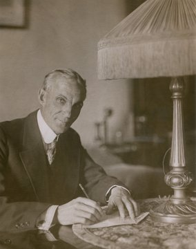 Henry Ford 1863-1947 signing a 10 000 check in aid of the Ford Peace Ship mission at the Hotel Biltmore