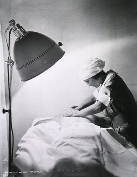 Nurse giving back rub to a patient in Walter Reed General Hospital