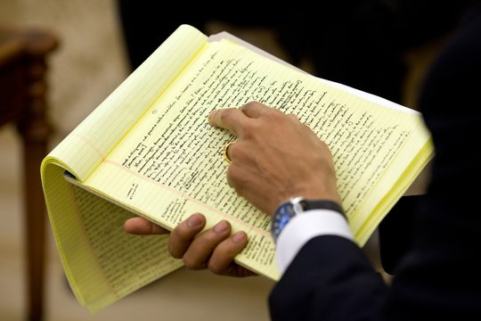 President Barack Obama holds his handwritten draft of the Nobel Peace Prize speech while working with his speechwriters