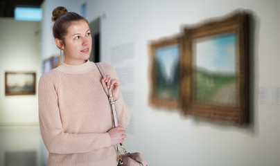 Woman standing near painting in art museum