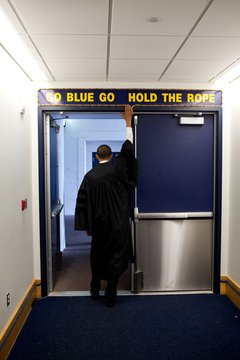 President Barack Obama touches the sign above the locker room door at Michigan Stadium before giving the commencement address to University of Michigan graduates in Ann Arbor Michigan