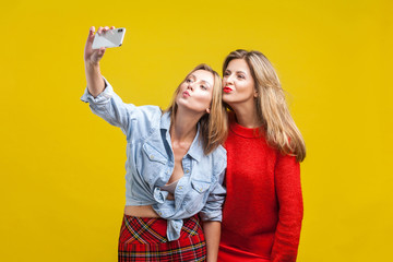 Female friends sending kiss while taking selfie. Portrait of two attractive women in stylish clothes standing, using smartphone to take funny photo. indoor studio shot isolated on yellow background