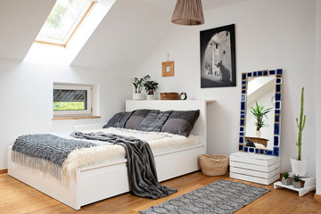 Interior of bedroom with modern design in the attic. White decor with grey decoration. Double bed with pillows, wooden furniture and picture on the wall. Scandinavian style in light indoors.