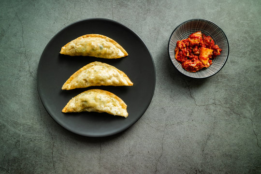 Traditional Korean fried mandu with kimchi on concrete background. Top view.