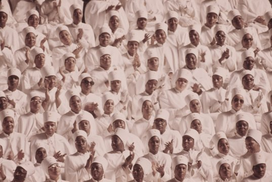 Black Muslim women dressed in white applaud Elijah Muhammad's Annual Savior's Day message. March 1974