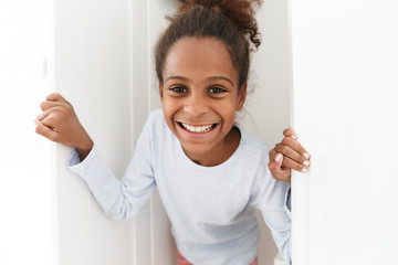 Image of african american little girl playing hide and seek in closet
