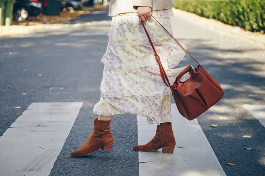 fashion blogger street style. fashionable woman posing wearing an oversized blazer, floral vintage dress, suede cowboy ankle boots and a black trendy mini handbag. perfect fall 2019 outfit.