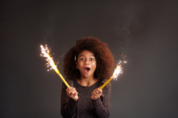 Cute festive girl with burning sparklers