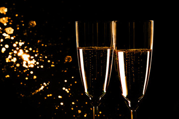 Glasses with champagne on black background, New Year background