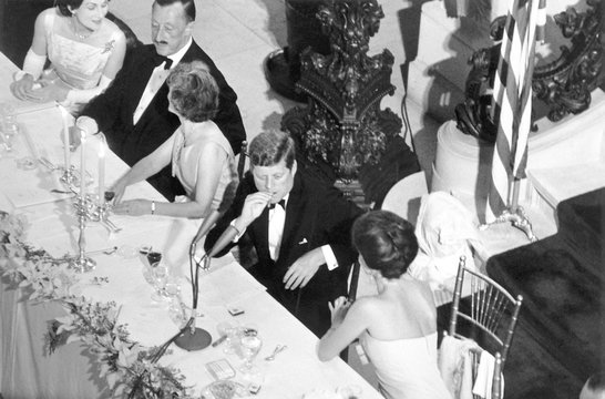 Jacqueline Kennedy leans over to talk with President Kennedy at the America's Cup Dinner.The dinner was held in the magnificent 'Breakers' mansion in Newport, Rhode Island. Sept. 14, 1962