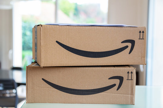 Close up of a stack of two Amazon Prime parcel boxes just being delivered with mail