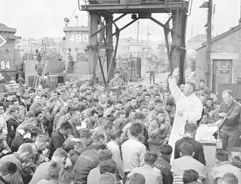 Catholic chaplain conducts services on a pier for first D-Day assault troops