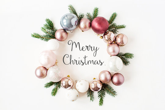 "Christmas / New Year holiday composition. Quote ""Merry Christmas"" in frame wreath with Christmas baubles, balls and fir branches on white background. Flat lay, top view festive concept."