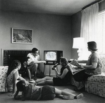 American family watching television in the living room of their home