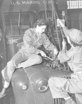 Women Marines lower a reconditioned engine back in place in a Marine Corps bus in 1943