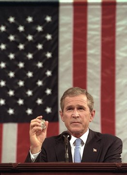 President George W. Bush holds the badge of a Port Authority Police officer killed on Sept. 11