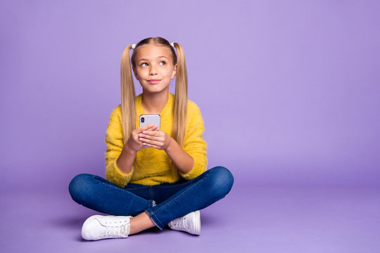 Full length photo of positive inspired kid sit legs crossed folded use cell phone think post look copyspace wear yellow pullover denim jeans sneakers isolated purple color background