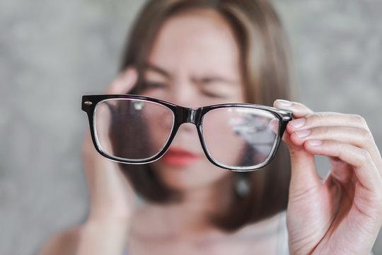 Asian woman holding eyeglasses having headache with eye blur vison