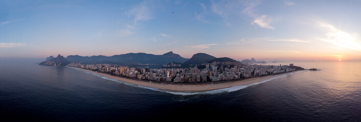 Canvas Prints Rio de Janeiro Aerial super wide panorama of Rio de Janeiro with Ipanema and Leblon beach in the foreground and the wider cityscape in the background against an orange and blue sky at sunrise