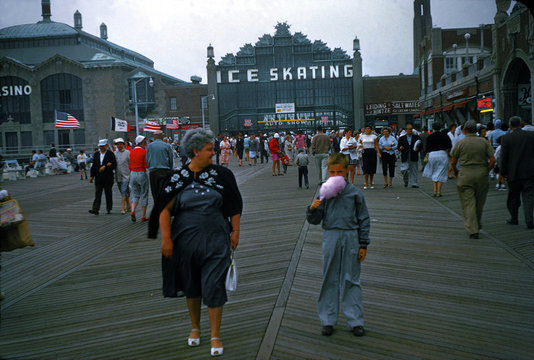 Asbury Park, on the boardwalk, Casino with ice skating rink in background, boy with cotton candy in foreground, New Jersey, circa 1960s
