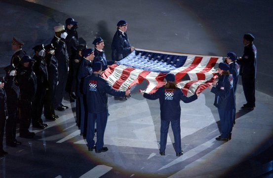 The US Olympic Team holds the American flag that flew over the Ground Zero on Sept. 11, 2001