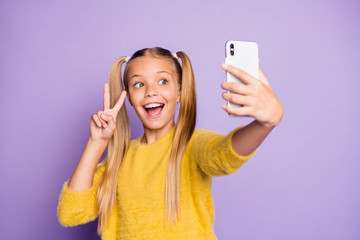 Portrait of funny funky child piggytails ponytails enjoy trip take selfie make v-signs wear stylish yellow pullover isolated over purple color background