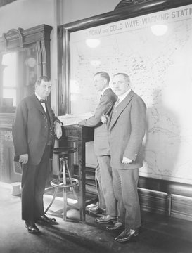 Meteorologists at the U.S. Weather Bureau stand in front of a map of the 48 states in 1924. Their