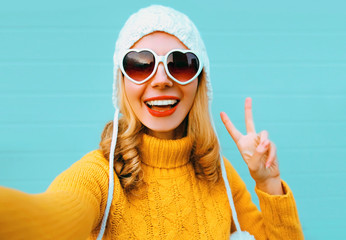Close up winter portrait of happy smiling woman stretching hand for taking selfie showing peace hand sign wearing yellow knitted sweater and white hat, heart shaped sunglasses on blue wall background