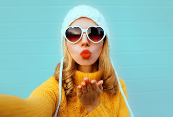 Close up winter portrait pretty woman blowing red lips sending sweet air kiss stretching hand for taking selfie wearing yellow knitted sweater, white hat, heart shaped sunglasses on blue background