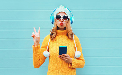 Photo sur Aluminium Magasin de musique Winter portrait cool woman with phone in headphones listening to music showing peace hand sign blowing red lips wearing yellow knitted sweater, white hat, heart shaped sunglasses on blue background