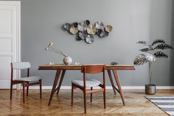 Modern and stylish dining room interior with glamour wooden table , elegant chairs and design decoration. Template. Home decor. Gray background wall.