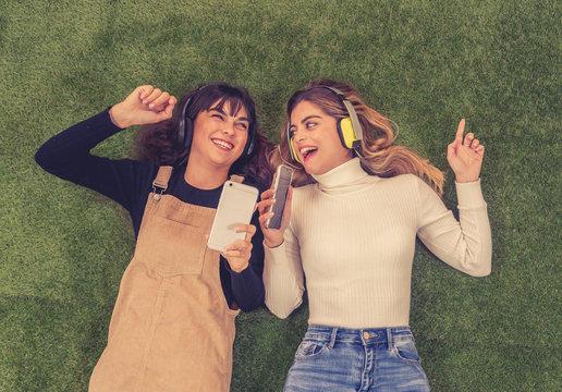 Pretty teenagers girl friends in headphones listening to music on their smart phones