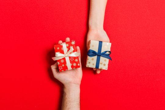 Top view of a woman and a man exchanging gifts on colorful background. Couple give presents to each other. Making surprise for holiday concept with copy space