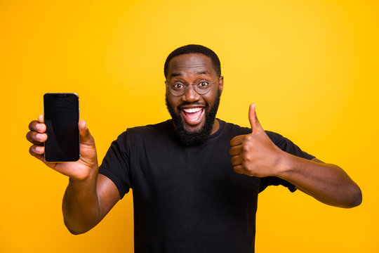 Great promo choose. Portrait of funny afro american man hold smartphone show thumb up sign advise select device suggest pick wear stylish t-shirt isolated yellow color background