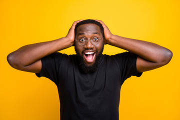Photo of cheerful positive funny cute black man overjoyed about discounted shopping mall grabbing his head with hands in t-shirt isolated vibrant color yellow background