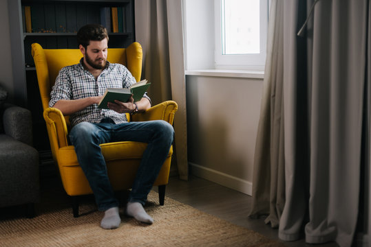 Confident young adult man with a beard reading a book by the window. Concept of everyday life.