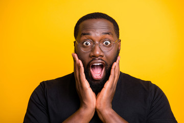 Close up photo of crazy screaming stupor black man in t-shirt expressing astonishment on face isolated bright color yellow background