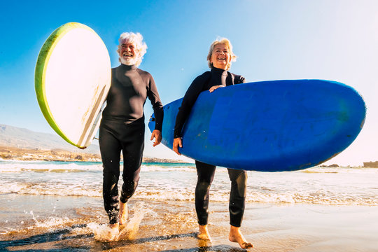couple of seniors at the beach with black wetsuits holding a surftable ready to go surfing a the beach - active mature and retired people doing happy activity together in their vacations or freetime