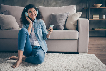 Photo of beautiful dark skin wavy lady closed eyes holding telephone wear cool earflaps listening new audio sitting floor near couch casual denim outfit living room indoors