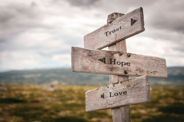 Trust hope and love text on wooden sign outdoors