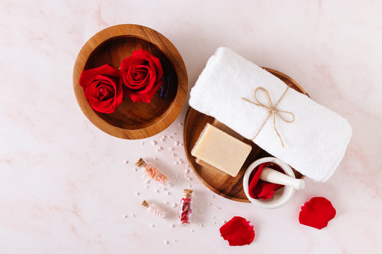 Spa product with rose oil and .Rose petals on white background.