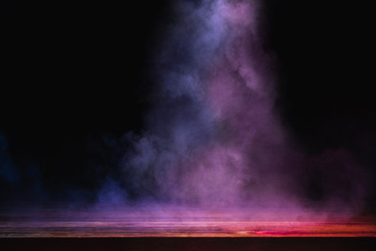 empty wooden table with colorful smoke float up on dark background