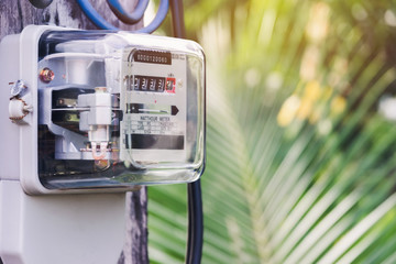 Electricity meter for house with sky background.